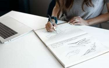 Mabble Media - Creative Agency | Art and Healing - women drawing hands in notebook on desk